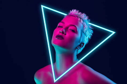 Future. Portrait of female fashion model in neon light with neoned blue glowing triangle on dark studio background. Beautiful woman with trendy make-up and well-kept skin. Vivid style, beauty concept.