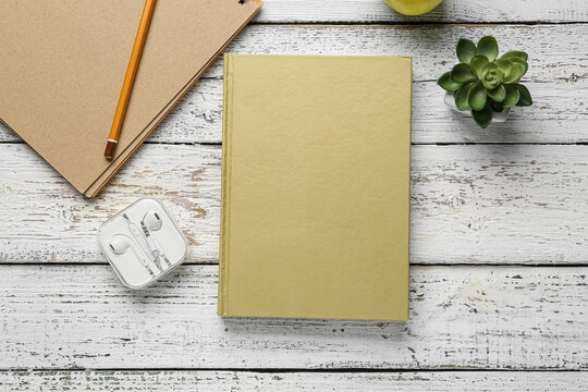 Blank book, earphones and plant on wooden background
