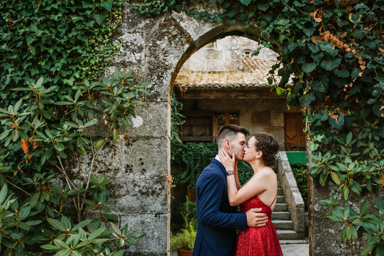 Elegant young couple on a luxurious building with vegetation