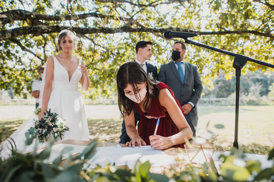 bridesmaid with surgical mask signing legal documents