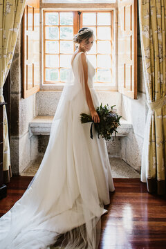 Bride on her wedding dress in front of a window
