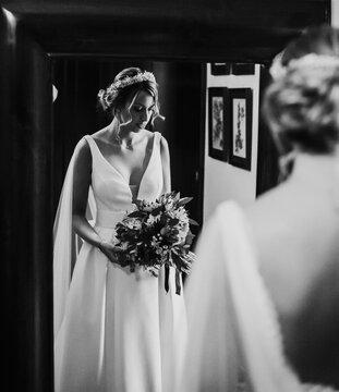 Bride looking herself in the mirror