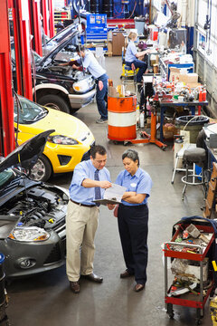 Owner of auto repair shop talks with Hispanic female mechanic as others work in background