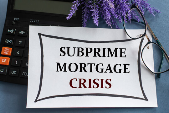SUBPRIME MORTGAGE CRISIS - words on a white sheet against the background of glasses, pens and lavender