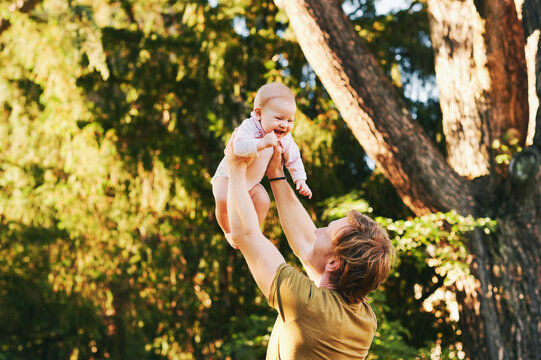 Happy young father playing with adorable baby girl in summer park, family lifestyle, dad holding kid high in the air