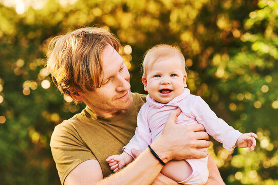 Outdoor portrait of happy young father with adorable baby