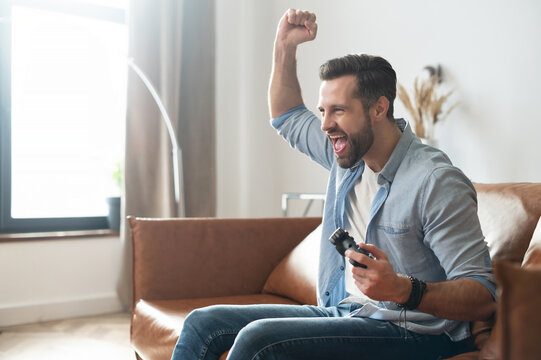 Side view a gambling guy with a joystick sitting on the couch, scream happily, won soccer on console. A bearded man spends leisure with a video game