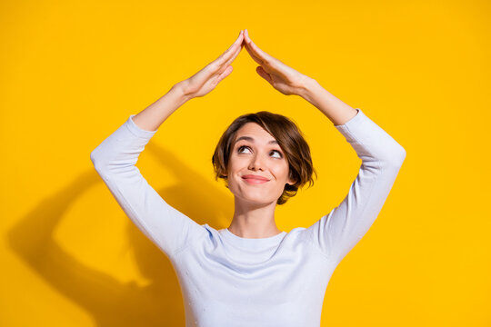 Photo portrait of woman making roof over head with hands isolated on bright yellow colored background