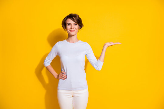 Photo of cheerful lady hand hold empty space arm hip wear white shirt pants isolated yellow color background