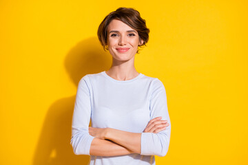 Photo of confident young woman folded hands look camera wear white shirt isolated yellow color...