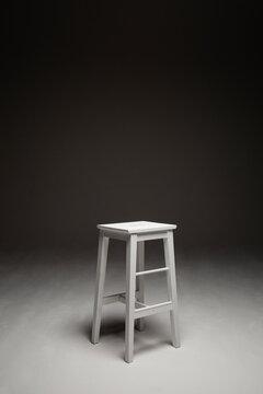 Wite stool in the studio in spotlight against dark background