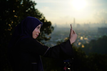 Side View Of Woman Taking Selfie While Standing Against Sky During Sunset