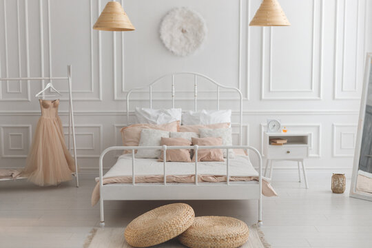 Scandinavian style bedroom with white metal bed, nightstand, and pastel color wall with stucco