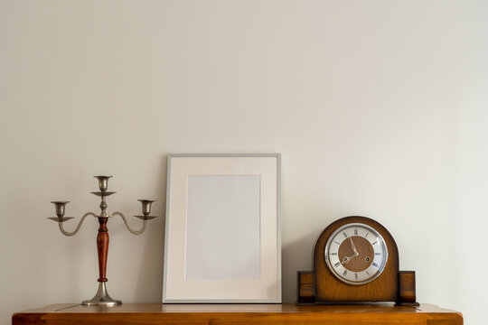Still life of Oak Cupbaords and top with Silver Picture frame Mock up and antique  wooden and silver candle stick  and old mechanical wind up clock