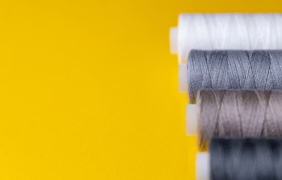 spools of colored thread lie in a row on a yellow background. Selective focus
