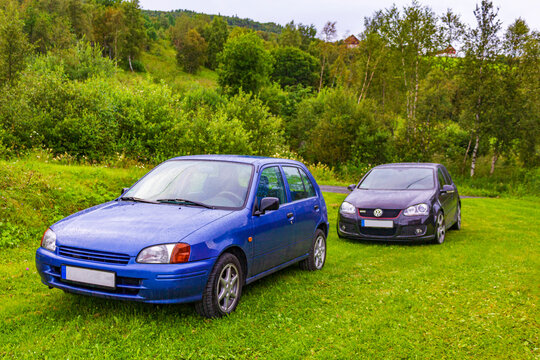 Black blue parked cars in the nature landscape of Norway.