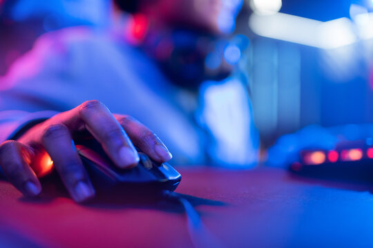 Professional cyber video gamer studio African American with personal computer armchair, keyboard for stream in neon color blur background. Soft focus
