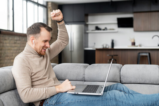 A young guy is watching sport match on the laptop, screams happily because his team is winning. Victory concept. Happy young man received good news on the email, got promoted, won in game