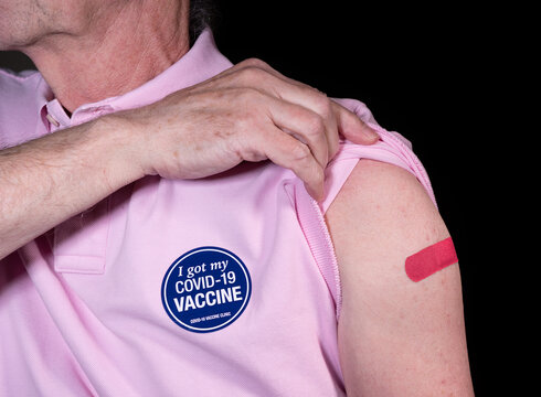 Senior adult man showing his adhesive plaster over his covid-19 vaccination with sticker saying he got his vaccine