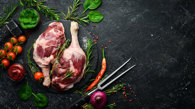 Poultry meat. Fresh raw duck thigh with rosemary and spices. On a black stone background. Top view.