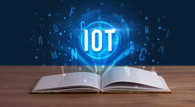 IOT inscription coming out from an open book, digital technology concept