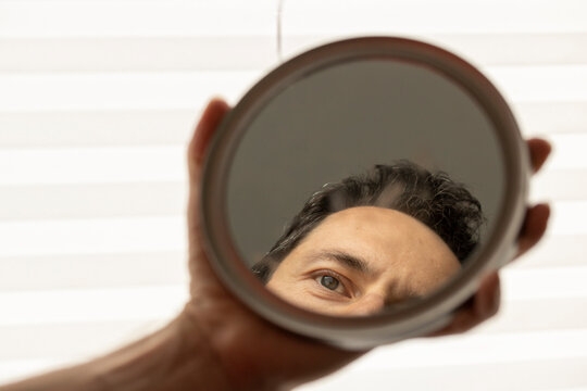 Cropped Hand Of Man Holding Mirror With Reflection