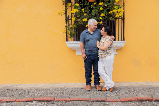 Adult couple embracing looking at each other on a yellow wall with flowers in Antigua Guatemala- Senior couple in love on vacation in colonial city