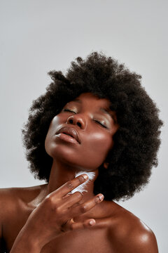 Portrait of sensual african american female model with afro hair touching her glowing bronzed skin with white feather, posing with eyes closed isolated over gray background