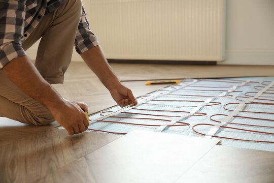 Professional worker installing electric underfloor heating system indoors, closeup