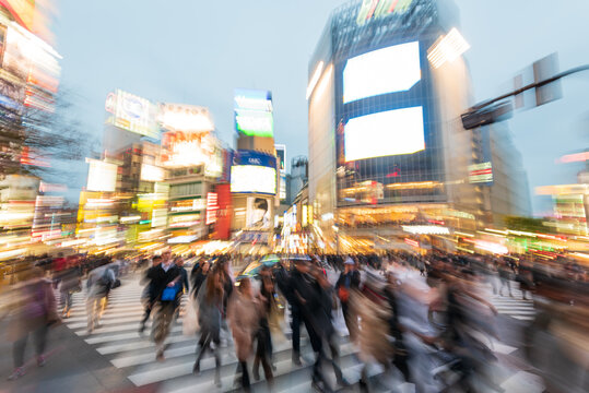 Tokyo, Japan - Janury 17, 2016: An abstract view of Commuters crossing one of the most famous crossings in Tokyo, the Shibuya crossing in Tokyo's shopping district. Lens Zoom effect during exposure.