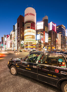 Tokyo, Japan - January 18, 2016: Taxi line up the The famous Ricoh billboard building during rush hour at night  at Ginza district at night and is one of the most famous city night views in Japan.