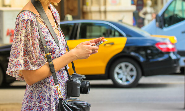 A girl in a floral summer sundress with a camera is typing a text message or looking for information on smartphone. Citizens on the street. The black and yellow cab in the background.