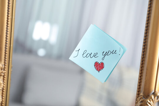 Note with phrase I Love You attached to mirror