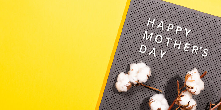 Grey plastic letter board with white quotes Happy Mother's Day, and cotton branch on a illuminating yellow background.