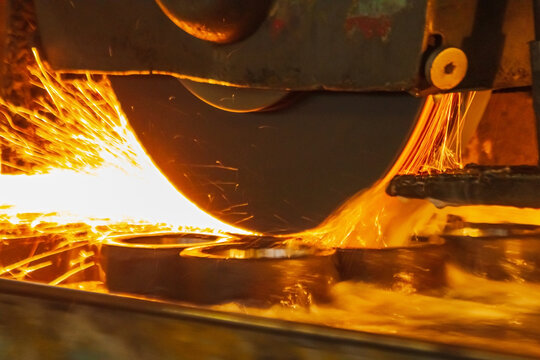 The surface grinder processes metal workpieces. Many sparks