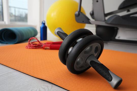 Ab roller and sport equipment near elliptical machine in gym