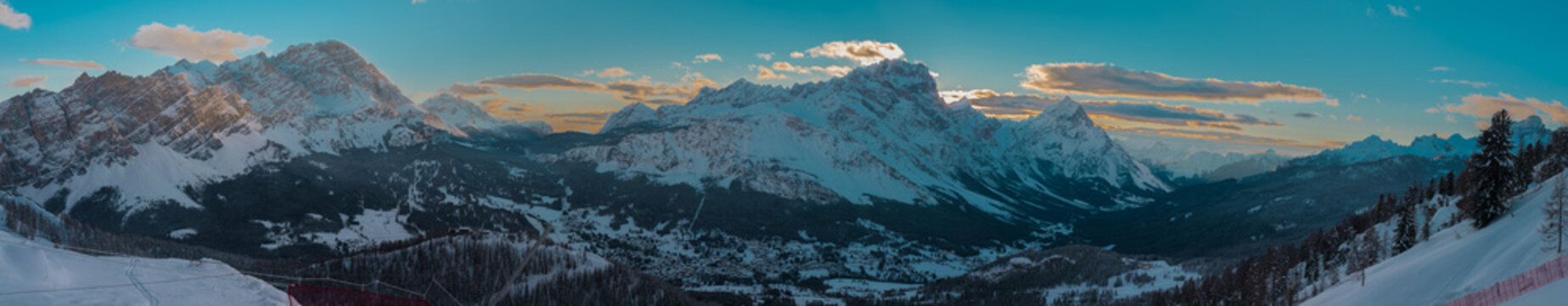 Early morning wide winter panorama of Valley around Cortina d'Ampezzo viewed from Tofana or ski piste above Cortina. Majestic mountains rising from the valley in sunrise.