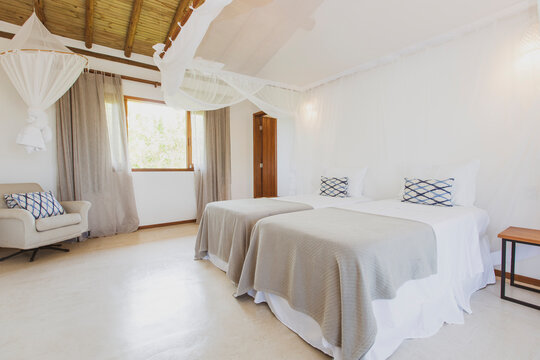 Modern luxury summer holiday or vacation wooden beach house bedroom interior with rustic canopy bed, white mosquito mesh net and glass window to the outdoors.
