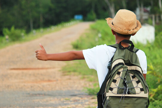 Rear View Of Boy With Backpack Hitchhiking While Standing On Road