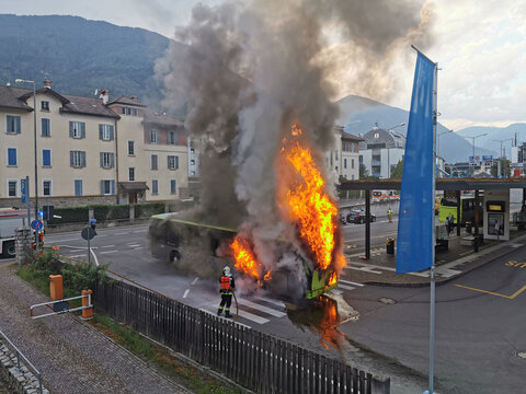 A large fire starts in the back of a bus just before it leaves the public station in the city center. Firefighter extinguish a burning public line bus. Public traffic bus on fire.