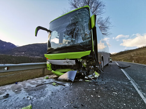 Violent frontal collision between a bus and a car traveling in the opposite direction. The destroyed front of a public transport bus after a head-on collision on a road.