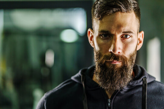 Front view close up portrait of young adult caucasian man with dark hair and beard in black shirt hoodie looking to the camera in dark - Confident modern male dramatic portrait with copy space