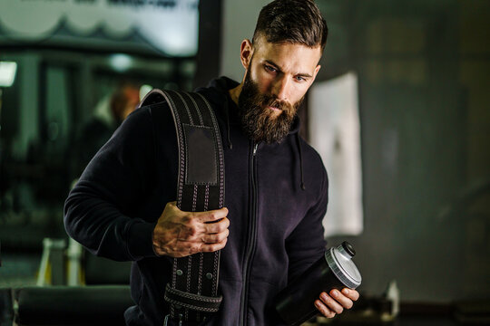 Front view portrait of young caucasian man athlete in black hoodie male standing in the gym holding protein supplement shaker and belt supplementation in training black hair and beard copy space
