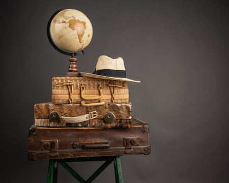 Closeup of vintage travel bags, a hat, and a world globe map on them - travel mood