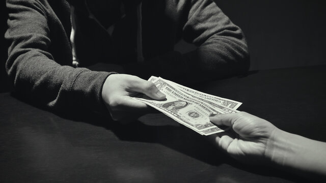 Cropped Hand Of Woman Bribing Man Against Black Background