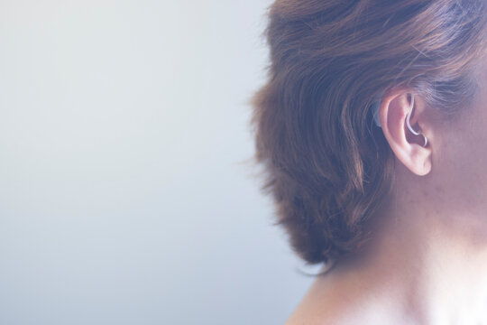 Close-up Man Wearing Hearing Aid Against Wall