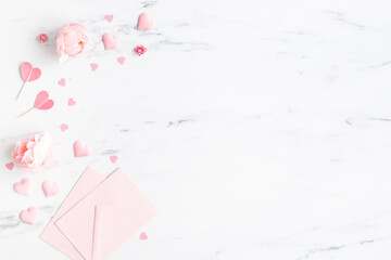 Valentine's Day background. Pink flowers, envelope, hearts on marble background. Valentines day...
