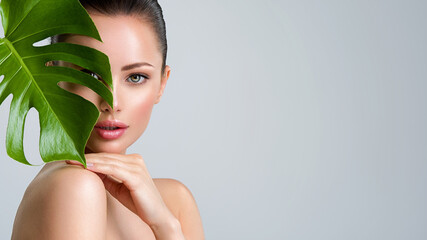 Fototapeta Beautiful woman with green leave near face and body.  Closeup girl's face with green leave. Skin care beauty treatments concept. obraz