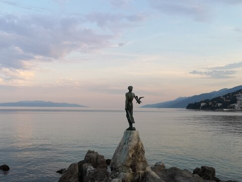 Maid Standing On Rock By Sea Against Sky During Sunset
