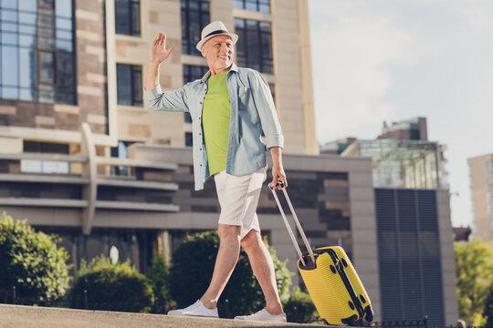 Photo of charming friendly mature man wear jeans shirt arm headwear holding baggage walking waving arm outside urban city street